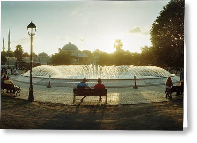Backlit Greeting Cards - People Sitting At A Fountain With Blue Greeting Card by Panoramic Images