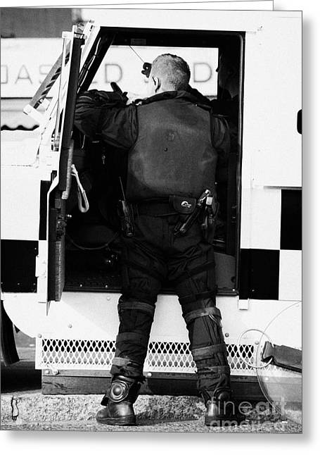 Terrorism Greeting Cards - PSNI officer puts on protective ruiot gear on crumlin road at ardoyne shops belfast 12th July Greeting Card by Joe Fox