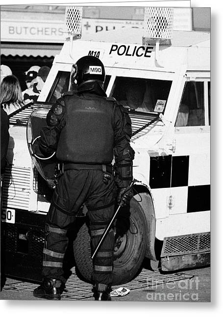 Terrorism Greeting Cards - PSNI officer with riot gear and baton in front of land rover on crumlin road at ardoyne shops belfas Greeting Card by Joe Fox