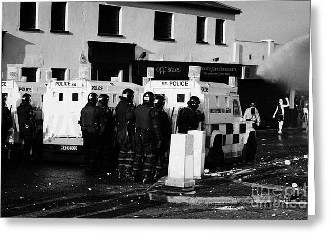 Terrorism Greeting Cards - PSNI officers watch rioters being hit by water canon on crumlin road at ardoyne shops belfast 12th J Greeting Card by Joe Fox