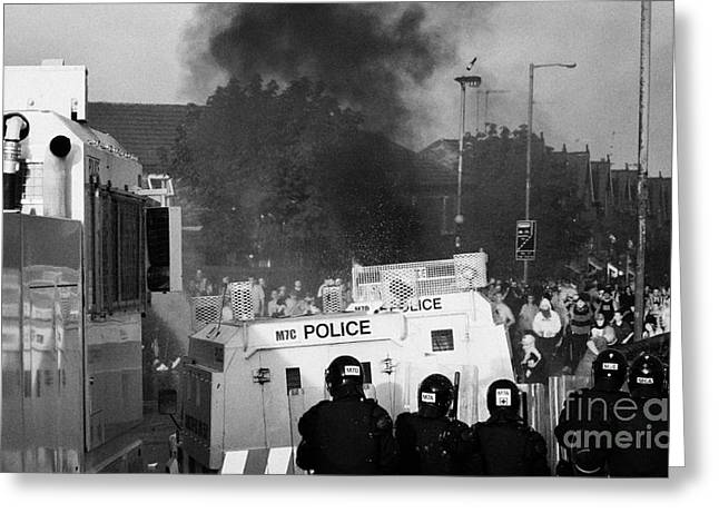 Protest Greeting Cards - PSNI riot officers face rioters mob and burning vehicle on crumlin road at ardoyne shops belfast 12t Greeting Card by Joe Fox