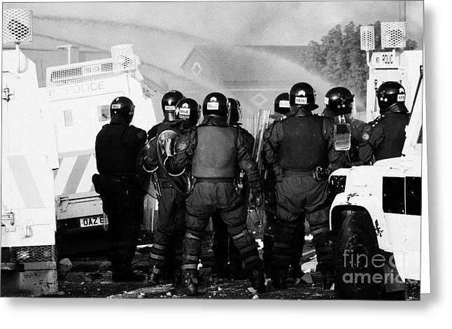 Protest Greeting Cards - PSNI riot officers watch rioting and water canon on crumlin road at ardoyne shops belfast 12th July Greeting Card by Joe Fox