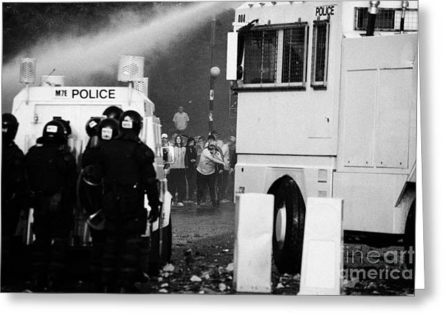 Terrorist Greeting Cards - PSNI riot police behind armoured land rover and water canon face on crumlin road at ardoyne Greeting Card by Joe Fox