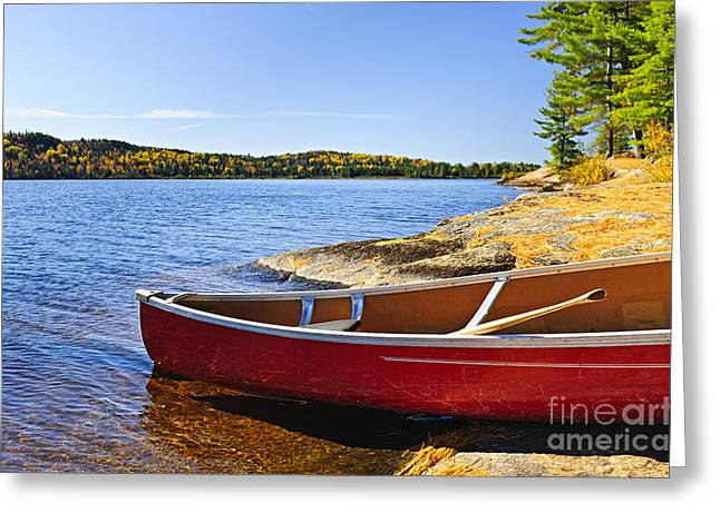 Canoe Greeting Cards - Red canoe on shore Greeting Card by Elena Elisseeva