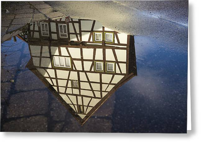 Raining Down Greeting Cards - Reflection of a beautiful old half-timbered house in a puddle of water Greeting Card by Matthias Hauser