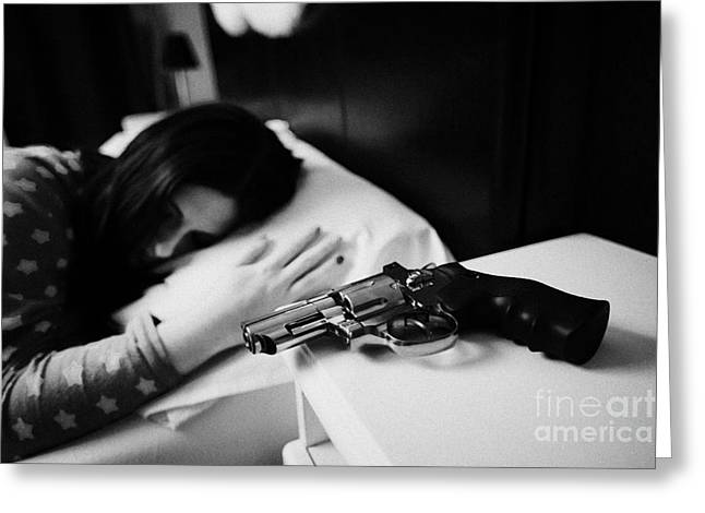 Bedside Table Greeting Cards - Revolver Handgun On Bedside Table Of Early Twenties Woman In Bed In A Bedroom Greeting Card by Joe Fox