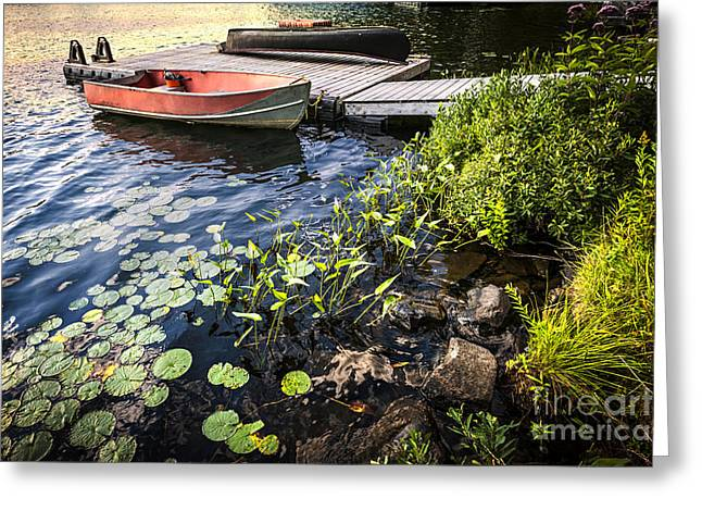 Canoe Greeting Cards - Rowboat at lake shore at dusk Greeting Card by Elena Elisseeva