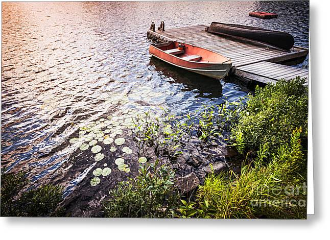 Wooden Boat Greeting Cards - Rowboat at lake shore at sunrise Greeting Card by Elena Elisseeva