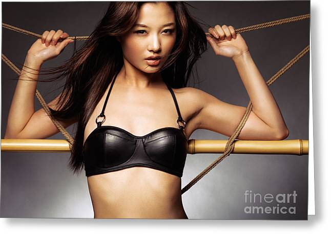 Worn Leather Photographs Greeting Cards - Sexy asian woman in black leather bra leaning against ropes Greeting Card by Oleksiy Maksymenko