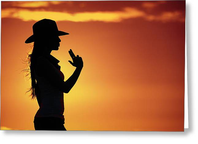 Satisfaction Greeting Cards - Sharp Shooting Cowgirl Silhouette  In A Hot Orange Western Sky Greeting Card by Kriss Russell