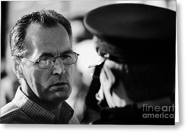 Protest Greeting Cards - Sinn Fein MLA Gerry Kelly talks to PSNI police officer on crumlin road at ardoyne shops belfast 12th Greeting Card by Joe Fox
