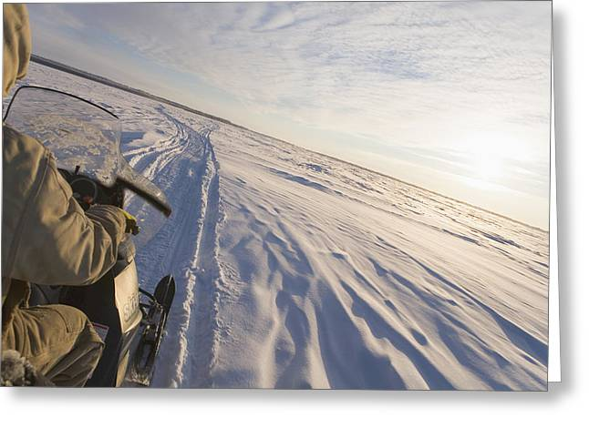 Drifting Snow Photographs Greeting Cards - Snowmachiner Following Trail On Frozen Greeting Card by Kevin Smith
