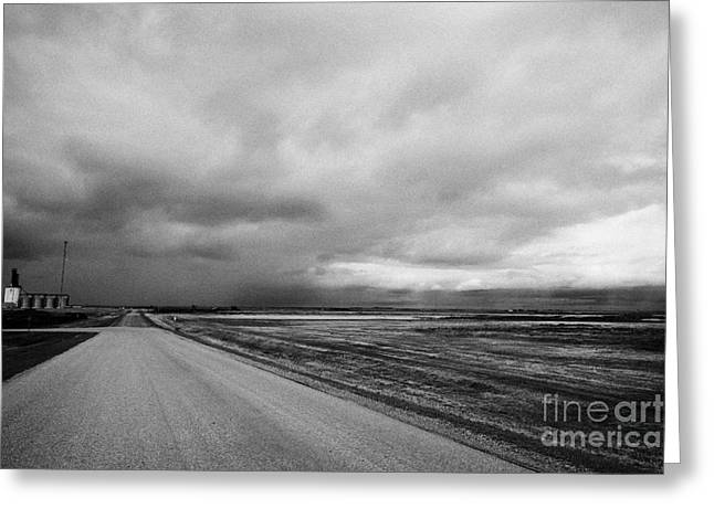 Winter Storm Greeting Cards - storm snow clouds forming over country road on the prairies assiniboia Saskatchewan Canada Greeting Card by Joe Fox
