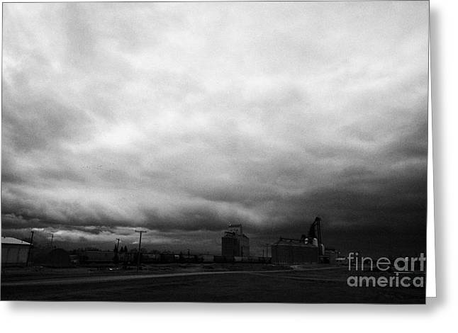 Winter Storm Greeting Cards - storm snow clouds forming over grain plant on the prairies assiniboia Saskatchewan Canada Greeting Card by Joe Fox