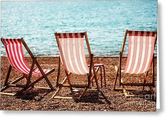 Sea View Greeting Cards - Stripy Deckchairs Pebble Beach Sea and Sunshine Greeting Card by Natalie Kinnear
