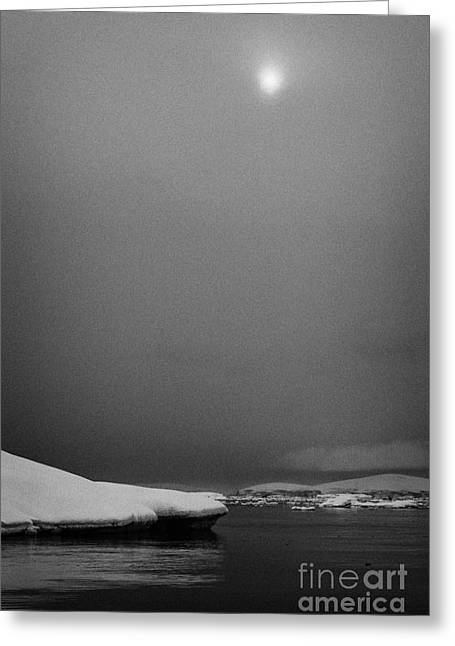 sun breaking through mist and cloud over snow covered ice shelf falling into the sea at Fournier Bay Greeting Card by Joe Fox