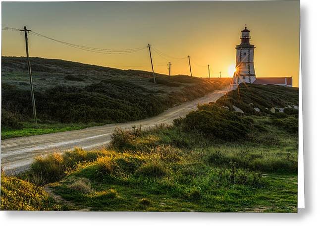 Sun Sets Behind The Lighthouse Greeting Card by Marco Oliveira