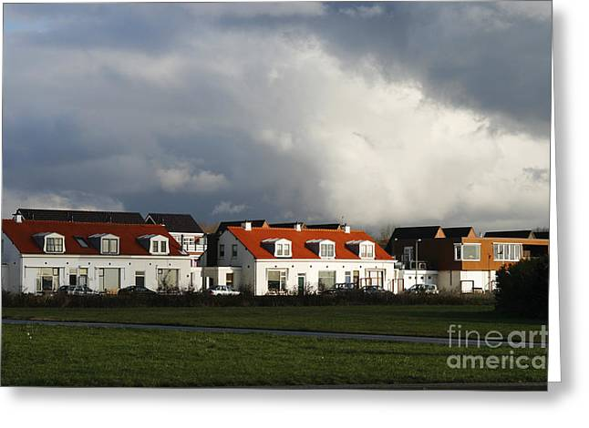 Ominous Sky Greeting Cards - Sunshine on houses under a thunder sky Greeting Card by Patricia Hofmeester