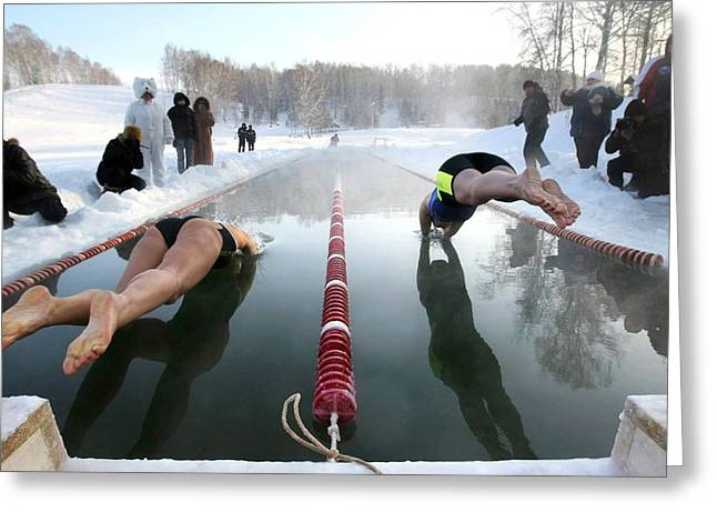 Swimmers Photographs Greeting Cards - Swimmers diving into ice-covered pool Greeting Card by Science Photo Library