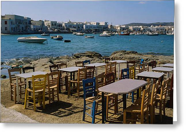 Empty Chairs Greeting Cards - Tables And Chairs In A Cafe, Greece Greeting Card by Panoramic Images