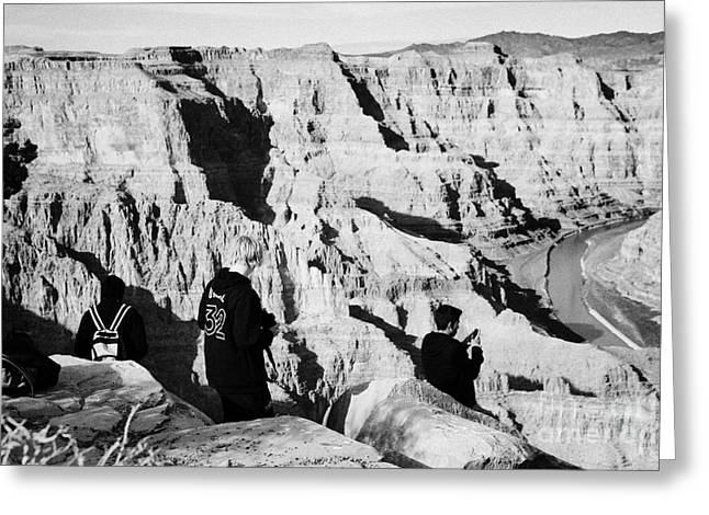 Man Looking Down Greeting Cards - teenage boys standing looking into the grand canyon and colorado river guano point Grand Canyon west Greeting Card by Joe Fox