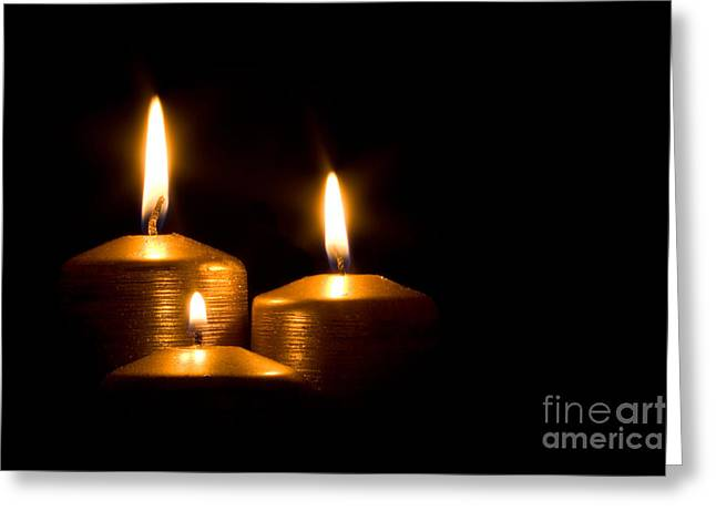 Festivities Greeting Cards - Three golden candles burning in the darkness Greeting Card by Jose Elias - Sofia Pereira