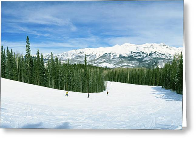 Three People Photographs Greeting Cards - Tourists Skiing On A Snow Covered Greeting Card by Panoramic Images