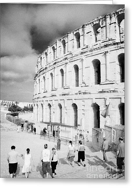 African Heritage Greeting Cards - Tourists Walk Down Steps Towards  The Main Entrance Of The Old Roman Colloseum Against Blue Cloudy Sky El Jem Tunisia Vertical Greeting Card by Joe Fox