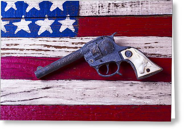 Steer Greeting Cards - Toy Gun On Wooden Flag Greeting Card by Garry Gay