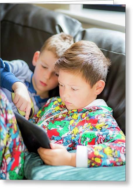 Two Boys Using A Digital Tablet Greeting Card by Samuel Ashfield