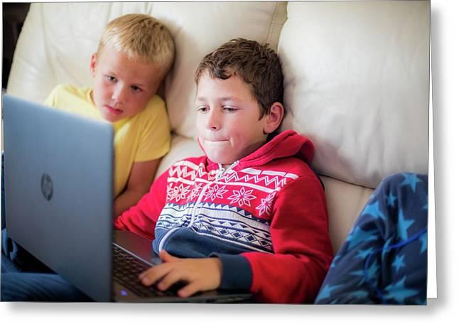 Two Boys Using A Laptop Sitting On Sofa Greeting Card by Samuel Ashfield
