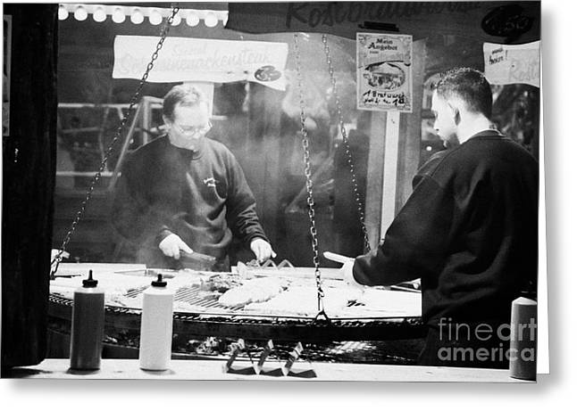 Berlin Germany Greeting Cards - Two men on a fast food meat selling stall cook rostbratwurst and steak on a huge open grill spandau christmas market Berlin Germany Greeting Card by Joe Fox