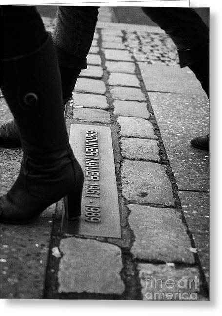 Berlin Germany Greeting Cards - two women walking across double row of bricks across berlin to mark the position of the berlin wall berliner mauer Berlin Germany Greeting Card by Joe Fox