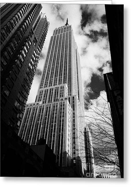 Manhatan Greeting Cards - View of the empire state building and surrounding buildings and  cloudy sky from West 33rd Street ny Greeting Card by Joe Fox