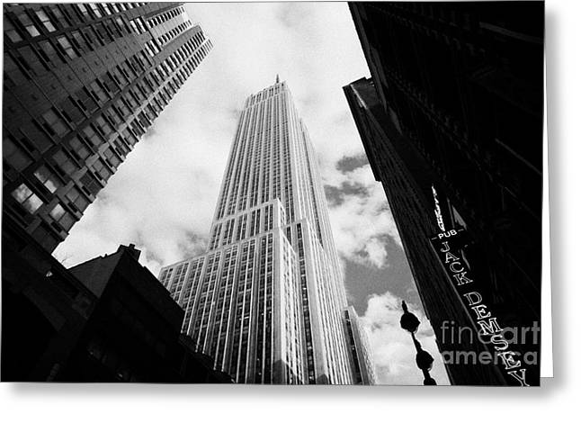 Manhatan Greeting Cards - View of the empire state building and surrounding buildings and cloudy sky West 33rd Street new york Greeting Card by Joe Fox