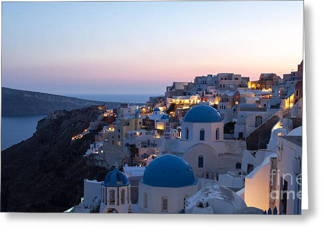 Cupola Greeting Cards - Village of Oia with blue domed churches at sunset Greeting Card by Matteo Colombo
