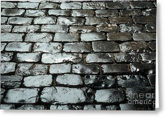 Street View Greeting Cards - Wet cobblestones on an old pavement Greeting Card by Bernard Jaubert