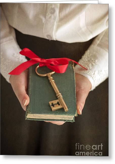 Satin Skirt Greeting Cards - Woman Holding A Book With A Key Tied With Red Ribbon Greeting Card by Lee Avison