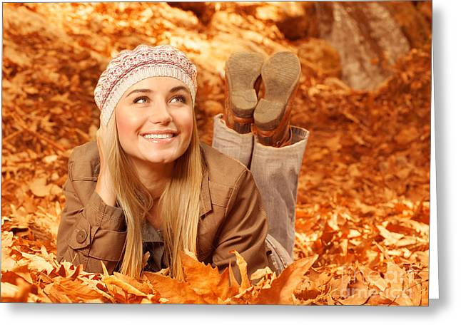 Lay Lady Lay Greeting Cards - Woman lay down on autumnal foliage Greeting Card by Anna Omelchenko