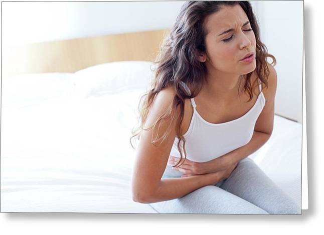 Woman On Bed With Cramps Greeting Card by Ian Hooton