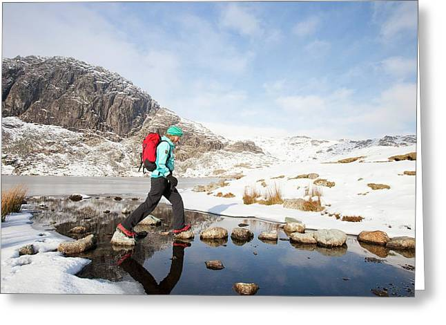 Woman Walker And Frozen Stickle Tarn Greeting Card by Ashley Cooper