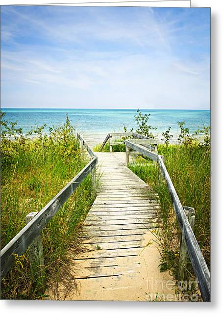 Sandy Greeting Cards - Wooden walkway over dunes at beach Greeting Card by Elena Elisseeva