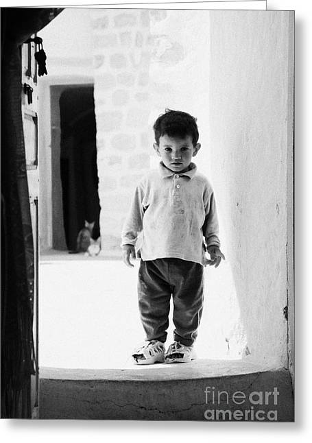 Dug Out Greeting Cards - young berber troglodyte boy standing in the entrance doorway to cave in underground dwelling at Matmata Tunisia Greeting Card by Joe Fox