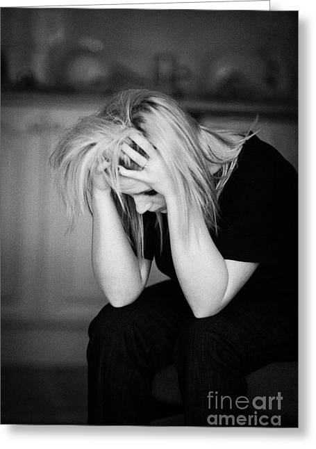 Despair Greeting Cards - Young Blonde Haired Teenage Woman Sitting With Head In Her Hands At Home In Her Kitchen Bedsit Greeting Card by Joe Fox
