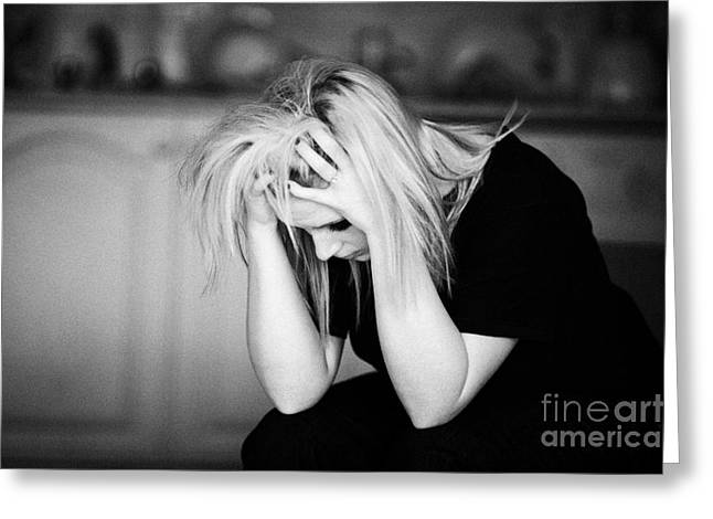 Concern Greeting Cards - Young Blonde Haired Teenage Woman Sitting With Head In Her Hands At Home In Her Kitchen  Greeting Card by Joe Fox