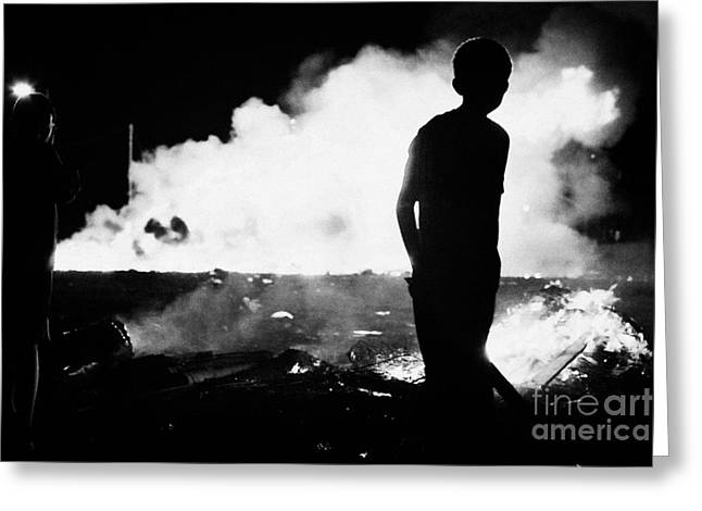 Protest Greeting Cards - young boy walks past 11th night bonfire in Monkstown fire northern ireland Greeting Card by Joe Fox