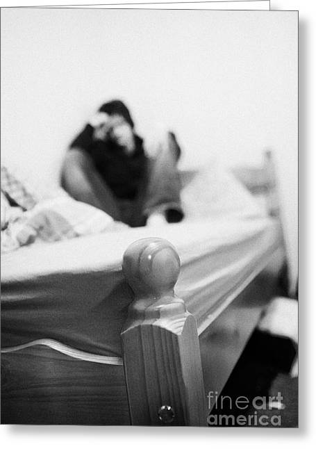 Despair Greeting Cards - Young Dark Haired Teenage Man Sitting At The Far End Of His Bed In An Untidy Bedsit Bedroom Curled U Greeting Card by Joe Fox