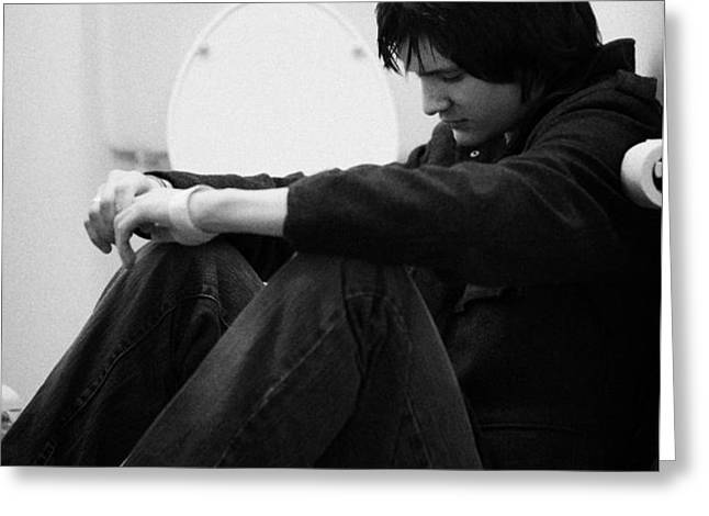 young dark haired teenage man sitting on the floor of the bathroom with back against the wall in the Greeting Card by Joe Fox