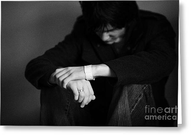 Despair Greeting Cards - Young Dark Haired Teenage Man Sitting On The Floor With Back Against The Wall In The Fetal Position  Greeting Card by Joe Fox
