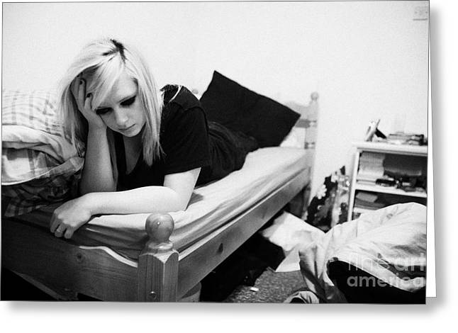 Despair Greeting Cards - Young Teenage Woman Lying On Bed In Messy Bedsit Bedroom Holding Her Head In One Hand Greeting Card by Joe Fox